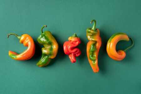 Ugly bell pepper on green background. Concept of zero waste production. Top view. Copy space. Non gmo vegetables.