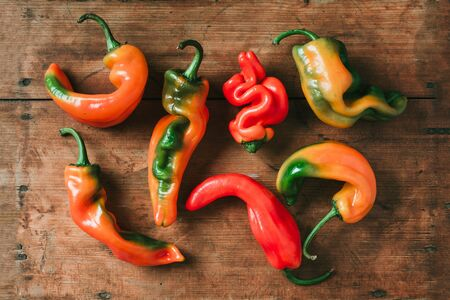 Ugly bell pepper on wooden background. Concept of zero waste production. Top view. Copy space. Non gmo vegetables