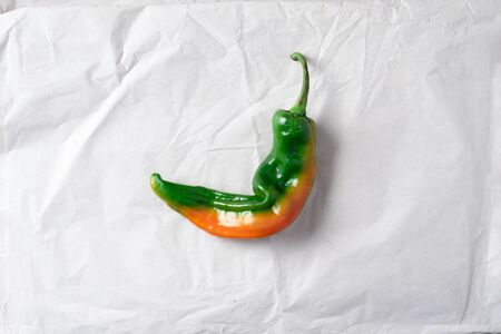 Ugly bell pepper on craft paper background. Concept of zero waste production. Top view. Copy space. Non gmo vegetables