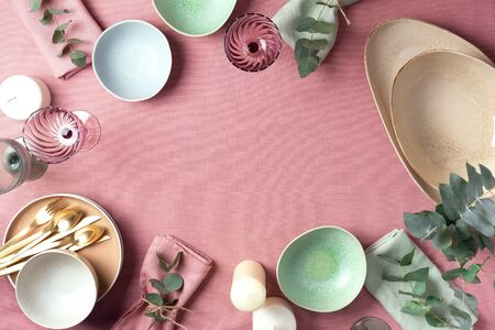 Table served for festive spring dinner. Top view. Copy space. Empty serving plates, bowls, candles and eucalyptus flowers on pink shabby background Stock Photo
