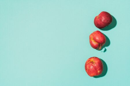 Ugly fruits concept. Organic red apples on blue background. The concept of ecology, not plastic. Healthy food. Copy space. Top view. Zero waste concept. Imagens