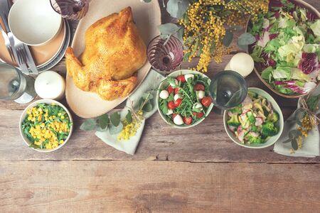 情人节,妇女节,母亲节,婚礼早午餐,节日家庭午餐和晚餐概念。节日家庭餐桌。服务板,碗用沙拉和菜盘,小吃,整个烤鸡,玉树,含羞草在木背景开花。