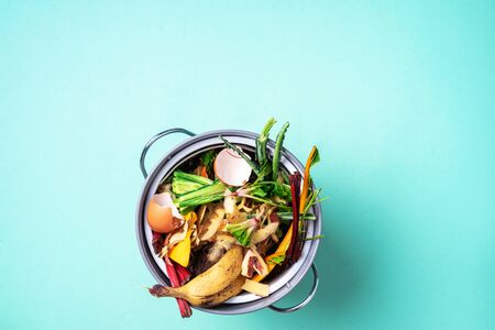 Peeled vegetables on chopping board, white compost bin on blue background. Top view of kitchen food waste collected in recycling compost pot Stock Photo