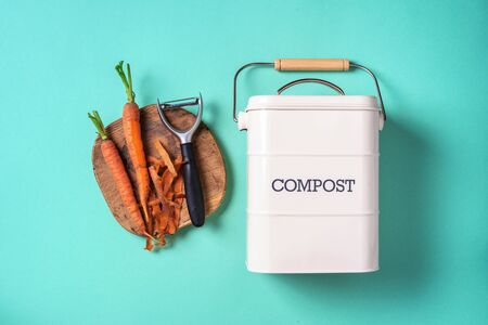 Top view of kitchen food waste collected in recycling compost pot. Peeled vegetables on chopping board, white compost bin on blue background. Stock Photo