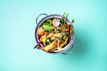 Recycle kitchen waste. Sustainable and zero waste living. Vegetable waste in recycling compost pot. top view. Copy space. Peeled vegetables on chopping board, white compost bin on blue background Stock Photo