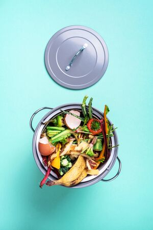 Sustainable and zero waste living. Vegetable waste in recycling compost pot. top view. Copy space. Peeled vegetables on chopping board, white compost bin on blue background. Recycle kitchen waste