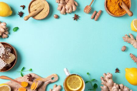 Organic ingredients for turmeric hot tea on blue background. Antiviral beverage. Healthy ayurvedic drink with lemon, ginger, cinnamon, turmeric. Immune boosting remedy.