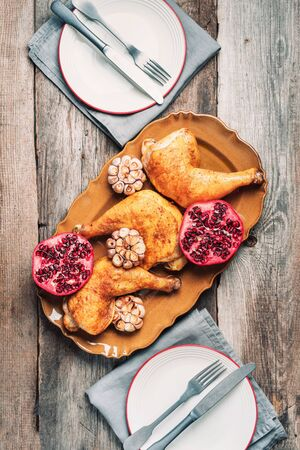 Traditional Thanksgiving day celebration party. Roasted chicken with pomegranate and garlic on wooden background. Friends or family dinner. Festive Christmas table. Top view.