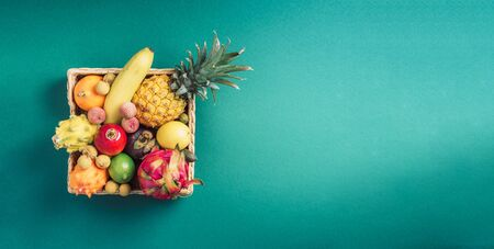 Rattan box full of exotic thailand fruits - pineapple, pitahaya, kiwano, african horned melon, tamarillo fruit, granadilla, feijoa, salak, snake fruits, maracuya, rambutan, lychee, longan, tamarind, mangosteen on green background. Top view, copy space. Vegan concept.