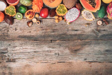Assortment of tropical fruits concept. Exotic fruits - pineapple, papaya, mango, annona, banana, pitahaya, kiwano, african horned melon, tamarillo fruit, granadilla, salak, snake fruit, maracuya, rambutan, lychee, longan, tamarind, mangosteen on wooden background. Top view Banco de Imagens