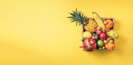 Rattan box full of exotic thailand fruits - pineapple, pitahaya, kiwano, african horned melon, tamarillo fruit, granadilla, feijoa, salak, snake fruits, maracuya, rambutan, lychee, longan, tamarind, mangosteen on yellow background. Top view, copy space. Vegan concept. Banco de Imagens