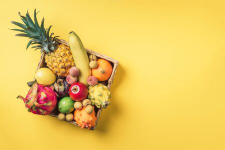 Tropical fruits on yellow background. Rattan box full of exotic thailand fruits - pineapple, pitahaya, kiwano, african horned melon, tamarillo fruit, granadilla, feijoa, salak, snake fruits, maracuya, rambutan, lychee, longan, tamarind, mangosteen. Top view, copy space. Vegan concept.