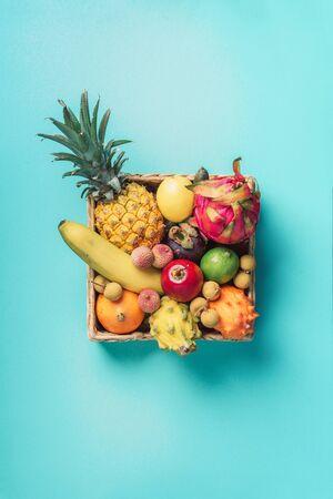 Tropical fruits on blue background. Rattan box full of exotic thailand fruits - pineapple, pitahaya, kiwano, african horned melon, tamarillo fruit, granadilla, feijoa, salak, snake fruits, maracuya, rambutan, lychee, longan, tamarind, mangosteen. Top view, copy space. Vegan concept. Banco de Imagens