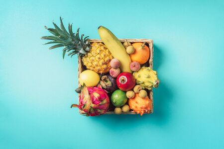 Rattan box full of exotic thailand fruits - pineapple, pitahaya, kiwano, african horned melon, tamarillo fruit, granadilla, feijoa, salak, snake fruits, maracuya, rambutan, lychee, longan, tamarind, mangosteen on blue background. Top view, copy space. Vegan concept. Banco de Imagens