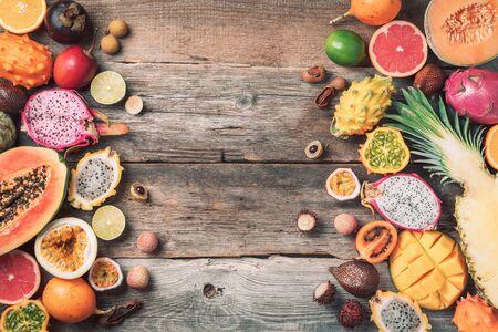 Tropical fruits concept. Exotic fruits - pineapple, papaya, mango, annona, banana, pitahaya, kiwano, african horned melon, tamarillo fruit, granadilla, salak, snake fruit, maracuya, rambutan, lychee, longan, tamarind, mangosteen on wooden background. Top view. Copy space