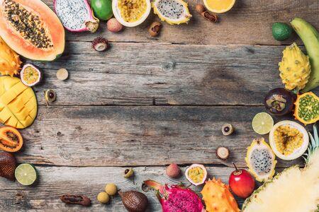 Exotic fruits - pineapple, papaya, mango, annona, banana, pitahaya, kiwano, african horned melon, tamarillo fruit, granadilla, salak, snake fruit, maracuya, rambutan, lychee, longan, tamarind, mangosteen on wooden background. Tropical fruits concept. Top view. Copy space