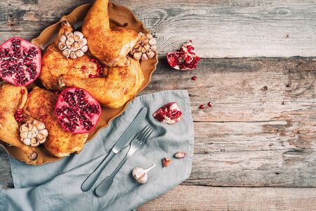 Roasted chicken with pomegranate and garlic on wooden background. Friends or family dinner. Festive Christmas table. Top view. Traditional Thanksgiving or Friendsgiving holiday celebration dish