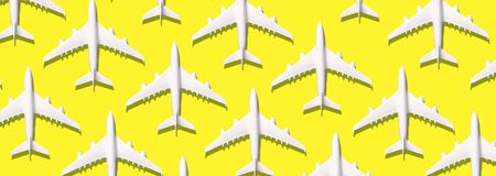Summer pattern. Creative banner of white planes on yellow background. Travel, vacation concept. Travel, vacation ban. Flights cancelled and resumed again. Top view. Flat lay. Minimal style design