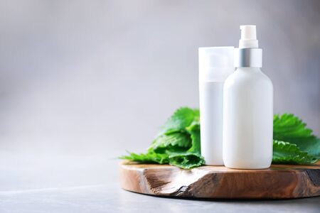 Natural spa, herbal cosmetics. Nettle lotion, cream, shampoo or soap in white bottle and fresh nettles leaves on grey background. Medicinal herb for health and beauty, skin care and hair treatment