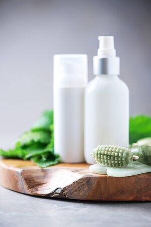 Skincare beauty routine at home bathroom. Face jade roller massager, nettle lotion, cream, shampoo in white bottles and nettles leaves. Medicinal herb for beauty, skin care and hair treatment