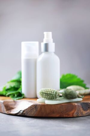 Face jade roller massager, nettle lotion, cream, shampoo in white bottles and nettles leaves. Medicinal herb for beauty, skin care and hair treatment. Skincare beauty routine at home bathroom 免版税图像