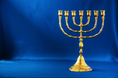 Golden hanukkah menorah on blue background. Jewish holiday banner with copy space. Ancient ritual religious candle menorah.