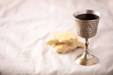 Unleavened bread, chalice of wine, silver kiddush wine cup on canva background. Communion still life. Christian communion concept for reminder of Jesus sacrifice. Easter passover.