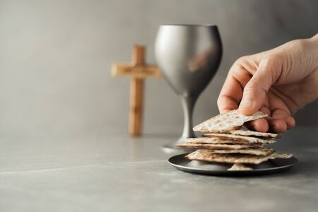 Hands with chalice and communion matzo bread, wooden cross on grey background. Christian communion for reminder of Jesus sacrifice. Easter passover. Eucharist concept. Christianity symbol and faith.
