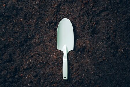 Small shovel with handel over soil background. Agriculture, organic gardening, planting or ecology concept