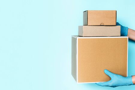 Contactless delivery, online shopping concept. Hand in medical glove gives craft box over blue background. Banner, copy space. Safe package during Coronavirus pandemic. Zero waste lifestyle. Reklamní fotografie
