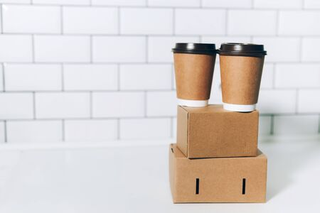 Craft paper cups with coffee to go and food box, lunch on tabletop over white kitchen. Banner, copy space. Safe delivery, take away only concept. Food delivery service during coronavirus pandemic.