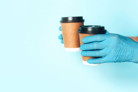 Coffee cup in hand with medical glove on blue background. Banner with copy space. Contactless delivery service during quarantine coronavirus pandemic. Take away only concept. Delivery service concept.