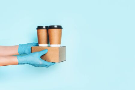 Hand in medical gloves carrying paper coffee cup coffee, lunch box on blue background. Banner, copy space. Contactless delivery service during quarantine coronavirus pandemic. Take away only concept.