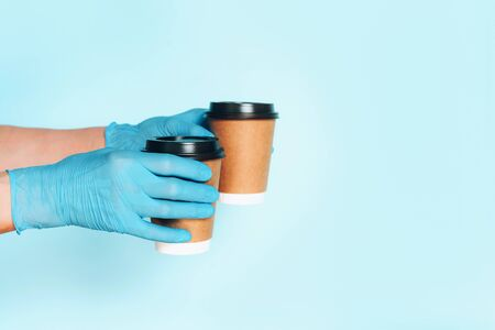 Hand in medical gloves carrying paper cup of takeaway coffee on blue background. Banner with copy space. Contactless delivery service during quarantine coronavirus pandemic. Take away only concept. Reklamní fotografie