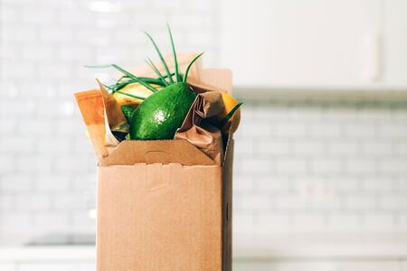 Food delivery service during coronavirus pandemic. Groceries box on white kitchen background with copy space. Online shopping. Food supplies, donation box, meal box concept. Stay home, stay safe.