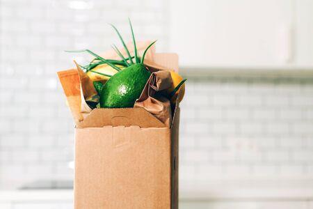Service de livraison de nourriture pendant la pandémie de coronavirus. Boîte d'épicerie sur fond de cuisine blanc avec espace de copie. Shopping en ligne. Approvisionnements alimentaires, boîte de dons, concept de boîte à repas. Restez à la maison, restez en sécurité.