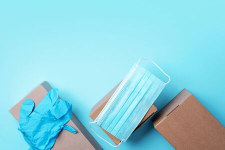 Craft paper cups, food box, gloves, bags, mask on blue background. Top view. Banner, copy space. Safe delivery, take away only concept. Food delivery service during coronavirus pandemic. Reklamní fotografie