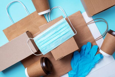 Craft paper cups, food box, gloves, bags, mask on blue background. Top view. Banner, copy space. Safe delivery, take away only concept. Food delivery service during coronavirus pandemic.