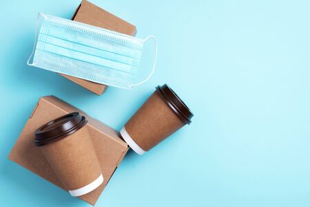 Craft paper cups with coffee to go and food box, lunch on blue background. Top view. Banner, copy space. Safe delivery, take away only concept. Food delivery service during coronavirus pandemic.