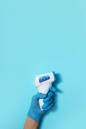 Hand in medical glove with digital infrared non contact thermometer gun for measuring temperature on blue background for coronavirus COVID-19 testing. Medicine concept. Quarantine pandemic. Stay safe. Banque d'images