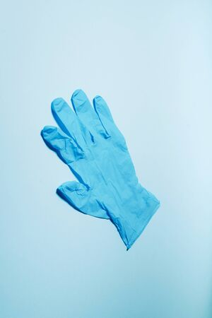 Protective medical glove on blue background. Top view. Copy space. Minimal medical concept. Medical equipment. Products to stay safe during pandemic covid19 quarantine Banque d'images