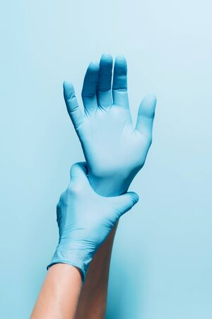 Woman doctor wears medical gloves over blue background. Copy space. National Doctors' Day. International Nurses Day. Health protection equipment during quarantine Coronavirus pandemic.