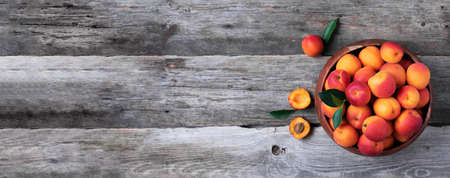 Ripe apricots with leaves on wooden background. Top view, copy space. Fruit banner. Healthy vegetarian food, detox or diet concept. Fruit summer concept. Bowl of harvested apricots for jam