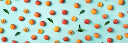 Apricot pattern on blue background. Top view, flat lay. Fresh summer fruit concept. Creative design. Healthy vegetarian food, detox or diet concept. Banco de Imagens