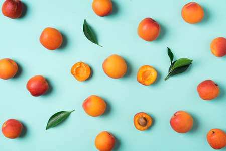 Apricot pattern on blue background. Top view, flat lay. Fresh summer fruit concept. Creative design. Healthy vegetarian food, detox or diet concept. Imagens
