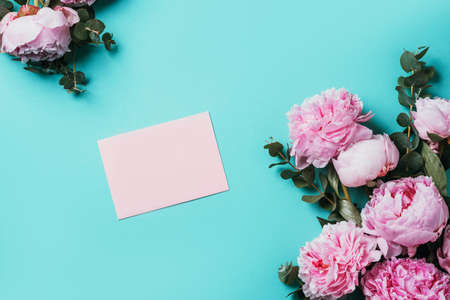 Feminine workspace with notebook, pink peony, eucalyptus flower on blue background. Top view, copy space. Blogger, feminine business concept. Flat lay. Birthday, Woman day. Mock up