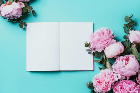 Fashion feminine blogger concept. Feminine workspace with notebook, pink peony, eucalyptus flower on blue background. Top view, copy space. Blogger, feminine business concept. Flat lay. Mock up