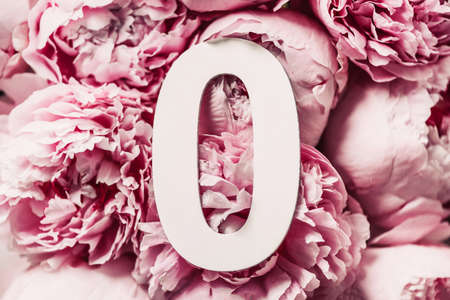 Creative layout. Pink peony flowers and number zero 0. Birthday greeting card. Anniversary concept. Top view. Copy space. Stylish white letter O over flowers background. Digit zero Standard-Bild