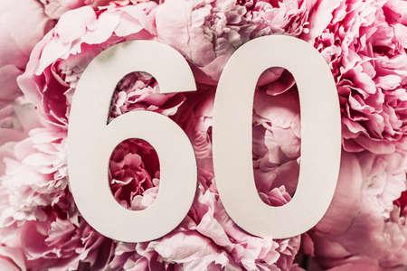 牡丹花,数字六十。生日与题字的贺卡60.周年纪念概念。顶视图。在花背景的白色标号。数值,庆祝活动,模板,传单