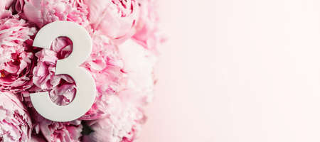 Creative layout. Pink peony flowers and digit three 3. Birthday greeting card. Anniversary concept. Top view. Copy space. Stylish white numeral over flowers background. Numerical digit. Фото со стока